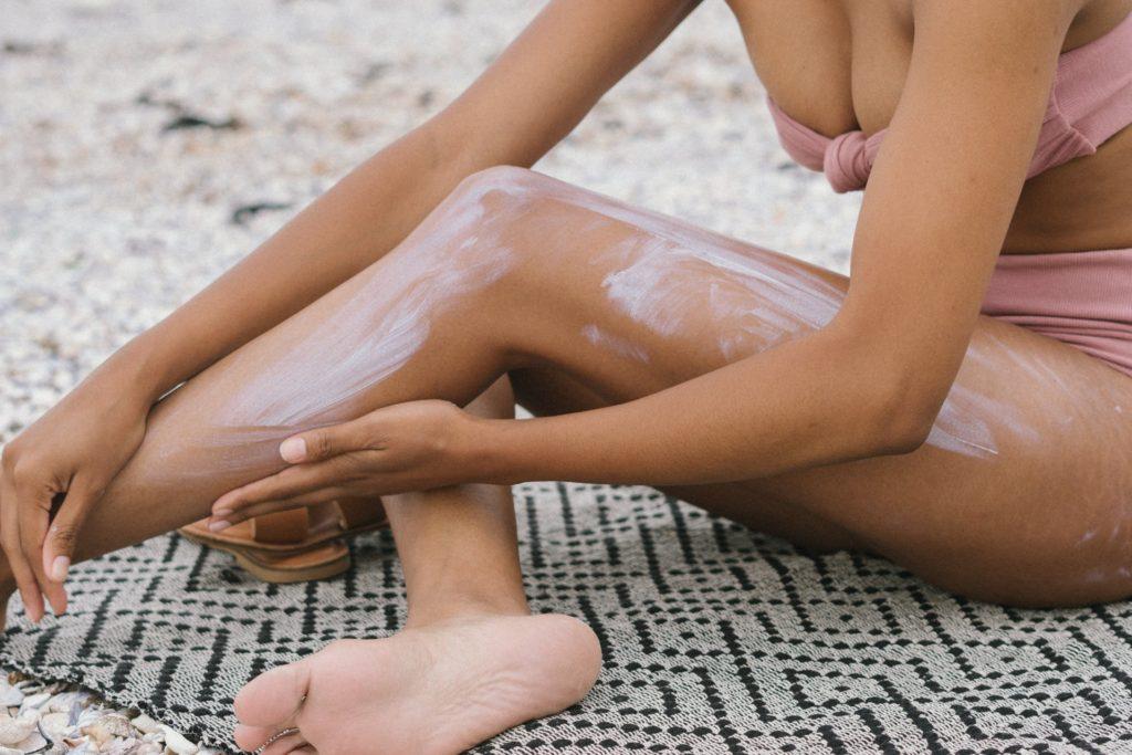 woman rubbing cream into leg