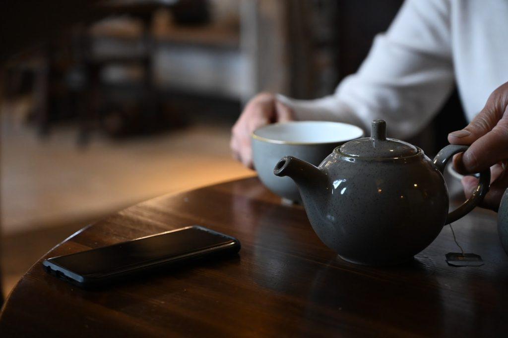 Pot of tea and a tea cup on a table in a cafe