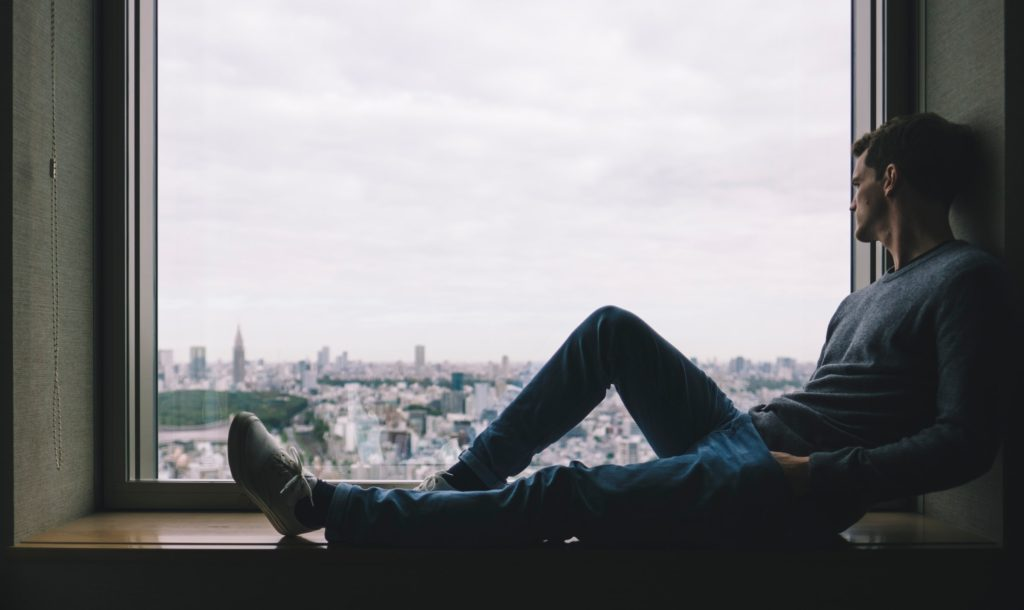 man looking out of a window waiting for soulmate
