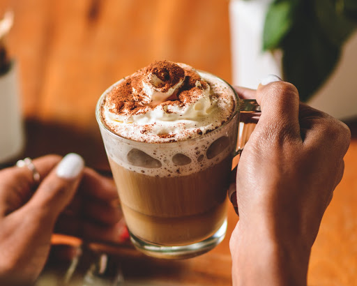 Person holding a orange Supermilk hot chocolate with whipped cream and chocolate sprinkles