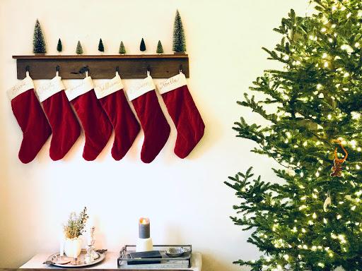 Six Christmas stockings hanging up next to a Christmas tree