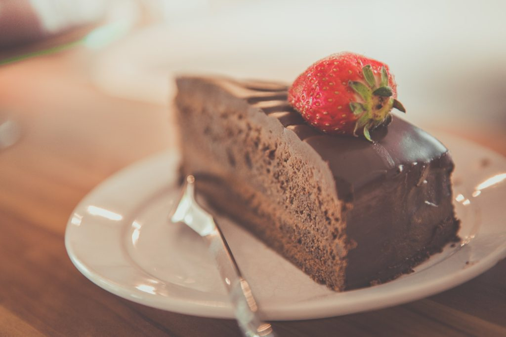 chocolate cake slice on a white plate with a strawberry on top