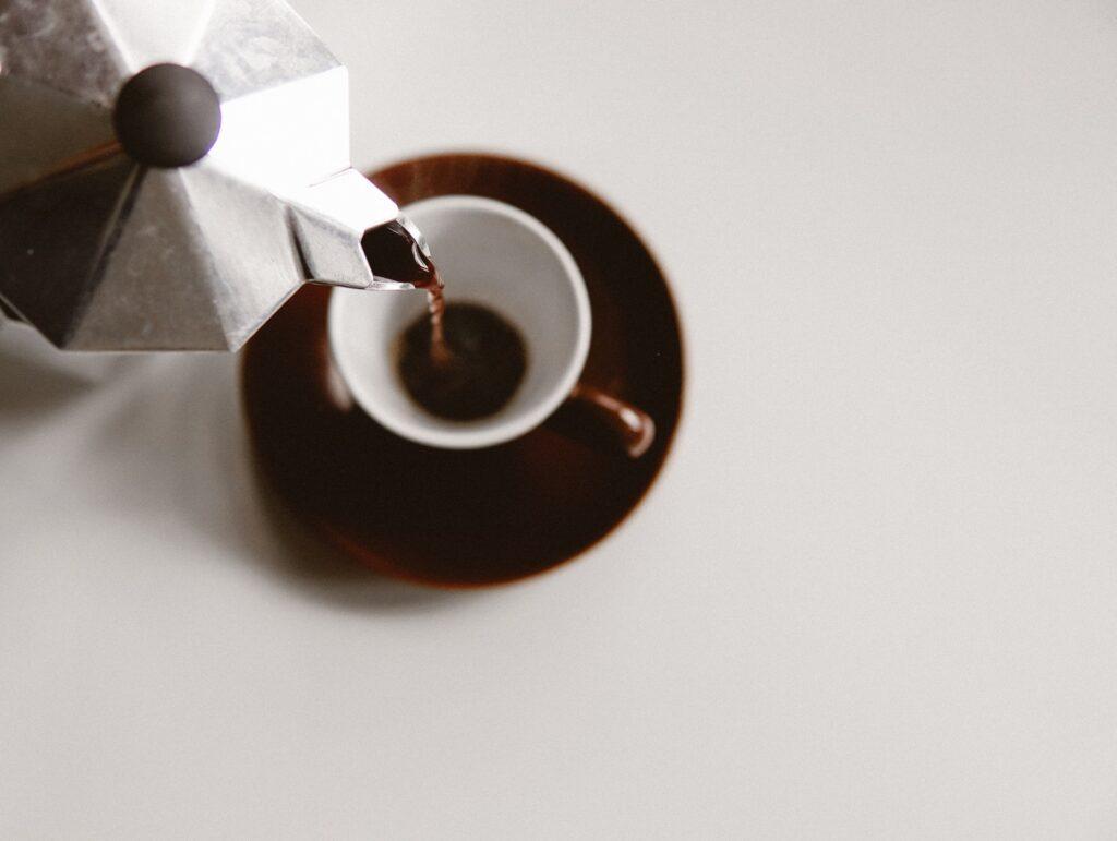 moka pot pouring coffee into an espresso cup