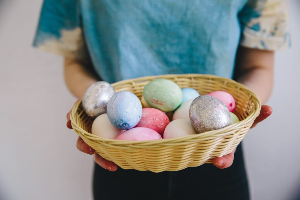 person gifting colourful eggs for easter
