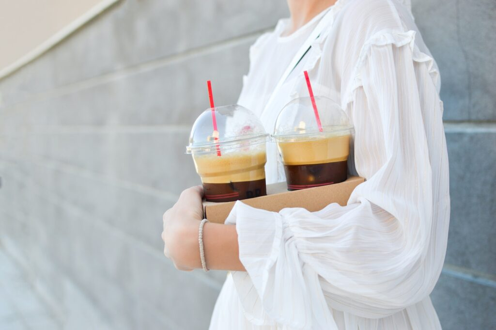 woman carrying two frappes in disposable cups