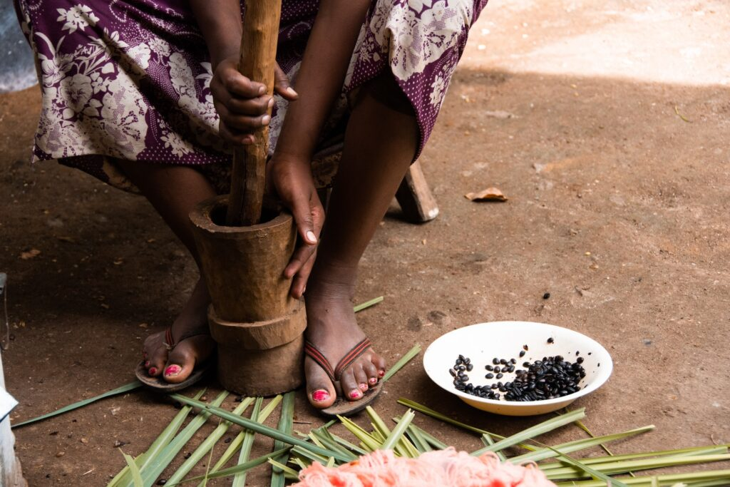 girl grinding coffee beans for an Ethiopian coffee ceremony